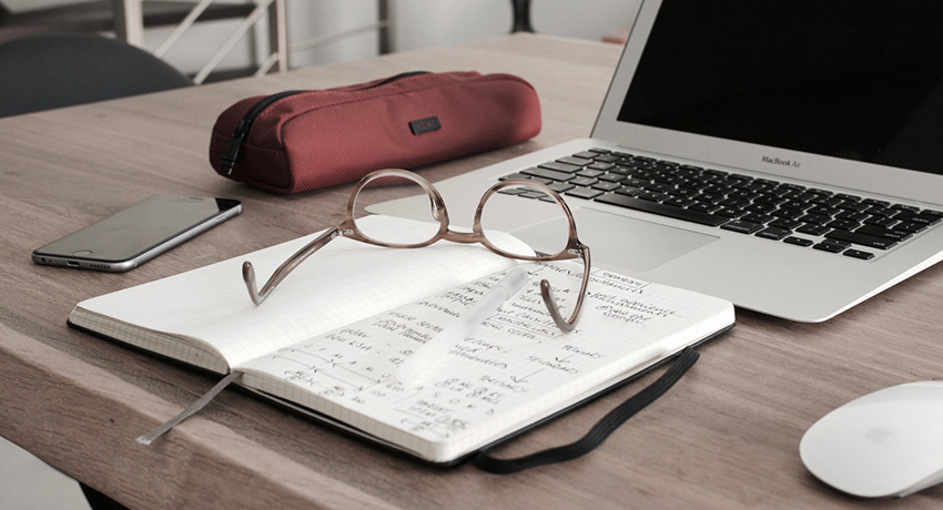 Desk with glasses and notepad